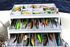 different fishing lures and baits in plastic box on wooden